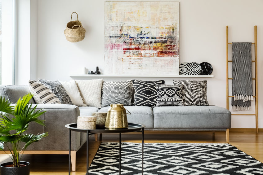 Patterned pillows on grey corner sofa in living room interior wi
