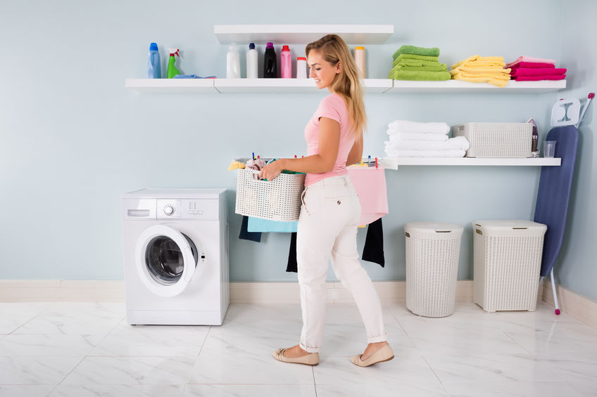 Woman With Basket Of Clothes In Utility Room